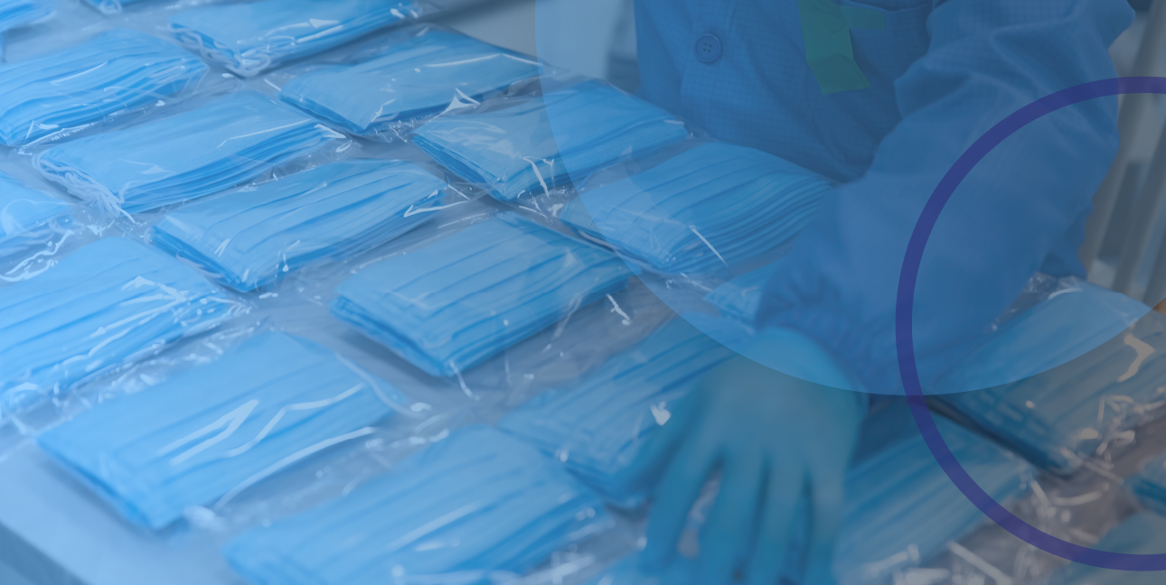 A gloved hand resting on packaged face masks in an assembly line.